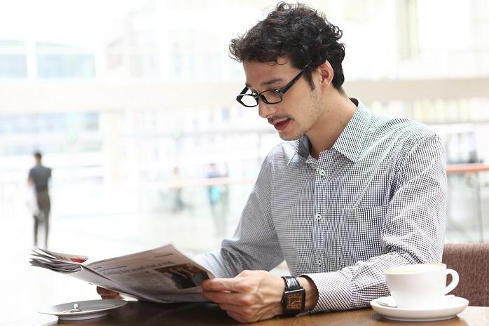 休日にカフェで新聞を読む男性