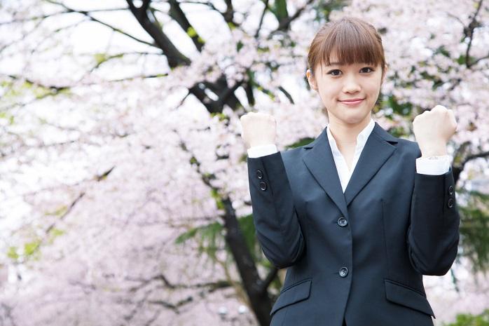 桜の前で記念撮影するOL