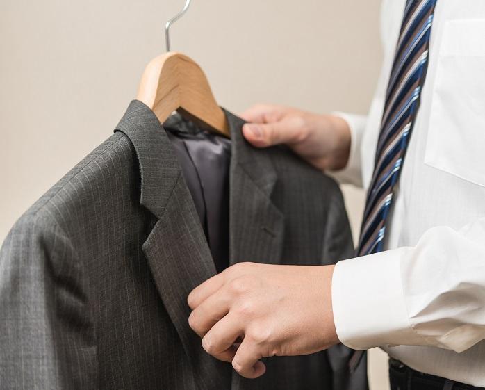 スーツをハンガーにかける男性