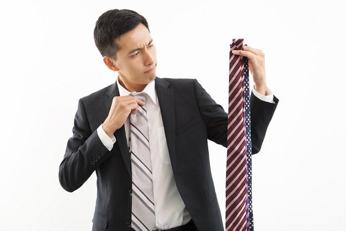 スーツにネクタイを合わせるサラリーマン