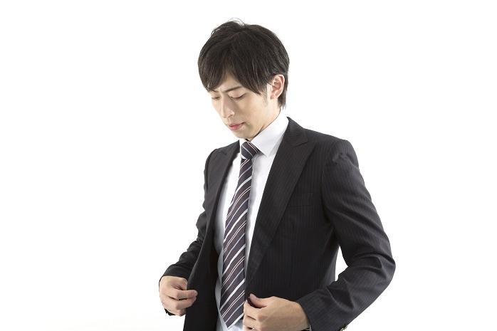 スーツのジャケットのボタンを留める男性